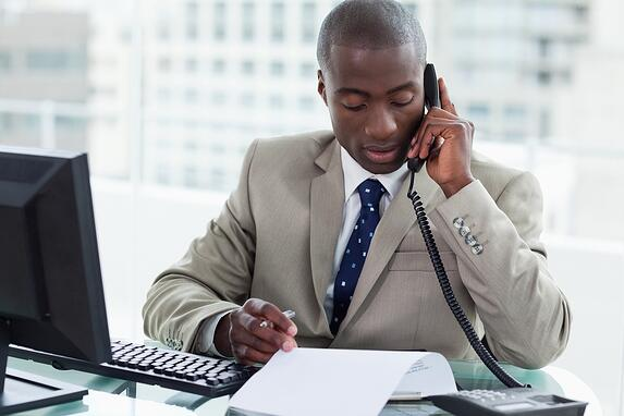 Entrepreneur making a phone call while reading a document in his office.jpeg
