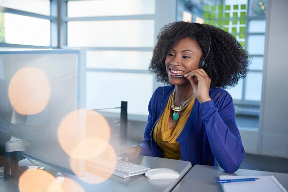 Portrait of a smiling customer service representative with an afro at the computer using headset.jpeg